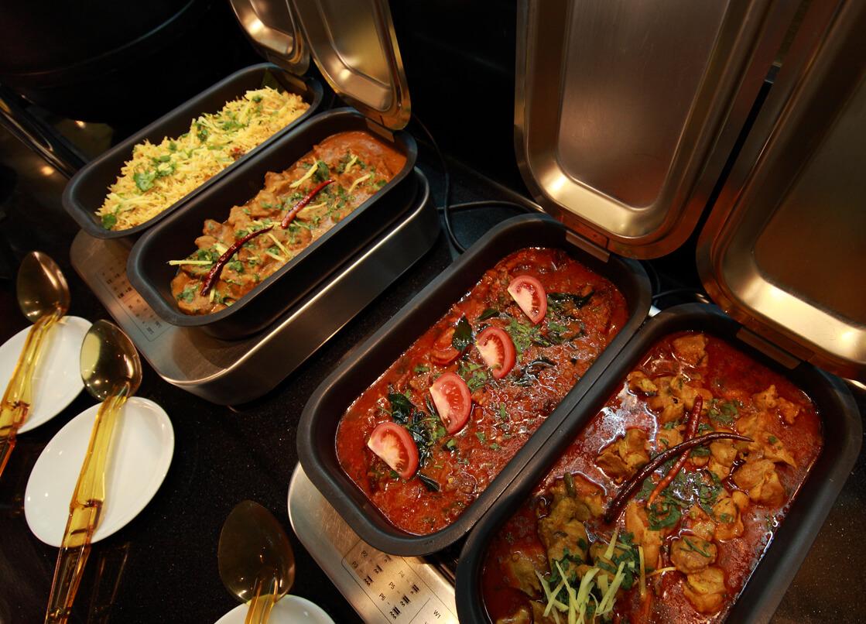 ビュッフェ形式で数種類のカレーや色とりどりの副菜が並びます